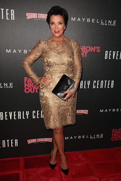 Kris Jenner vestido dourado em renda com scarpin preto e bolsa de mão.