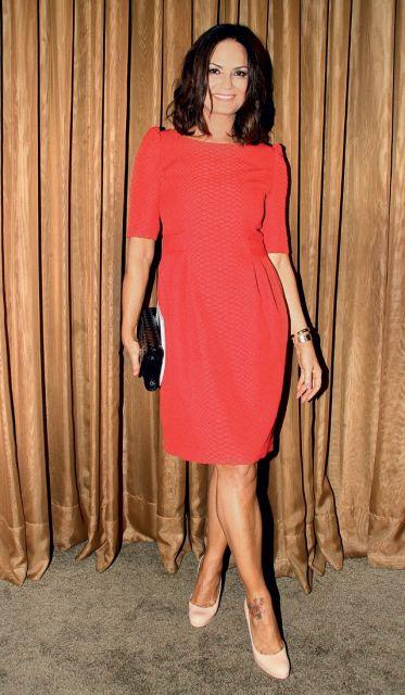 Luiza Brunet usa vestido vermelho liso meia manga com bolsa preta de mão e sapato nude.
