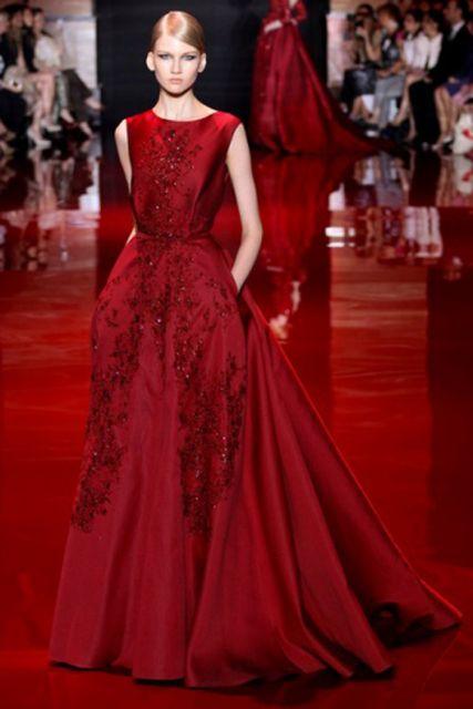 Modelo veste vestido vermelho longo rodado com decote fechado, modelo regata.