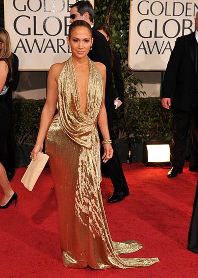 Jlo veste vestido dourado com decote mega ousado e bolsa nude.