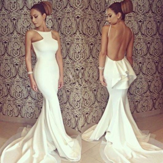 Modelo veste vestido branco longo com decote nas costas profundo.