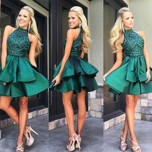 Modelo usa vestido verde com renda, brinco de strass branco e sapato de salto bege claro.