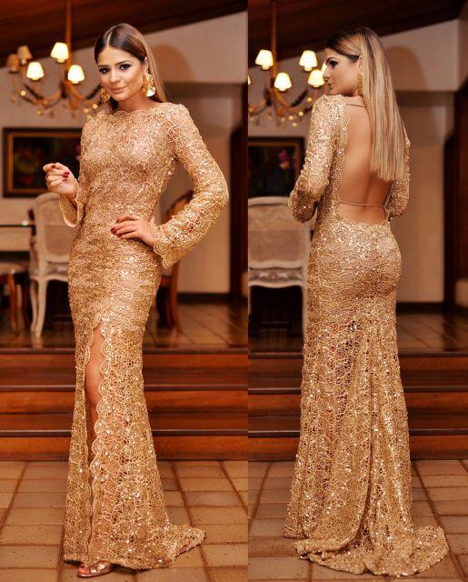 Thássia Naves veste vestido dourado bordado, manga longa com decote nas costas e fenda.