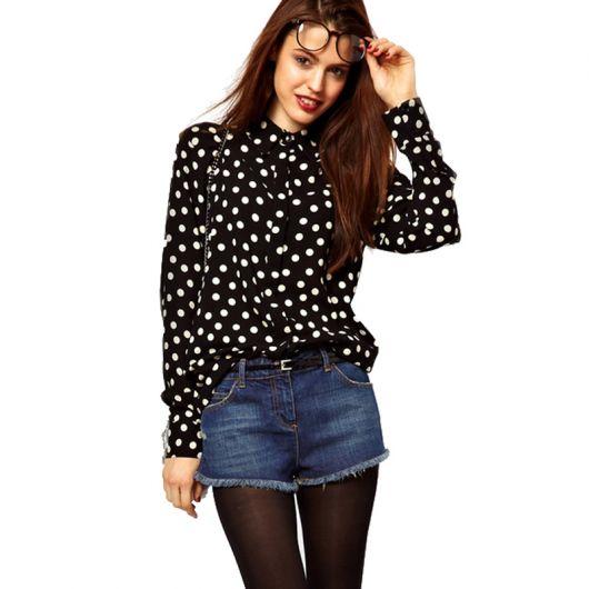 modelo usa blusa preta com bolinhas brancas short jeans azul escuro e meia fina na
