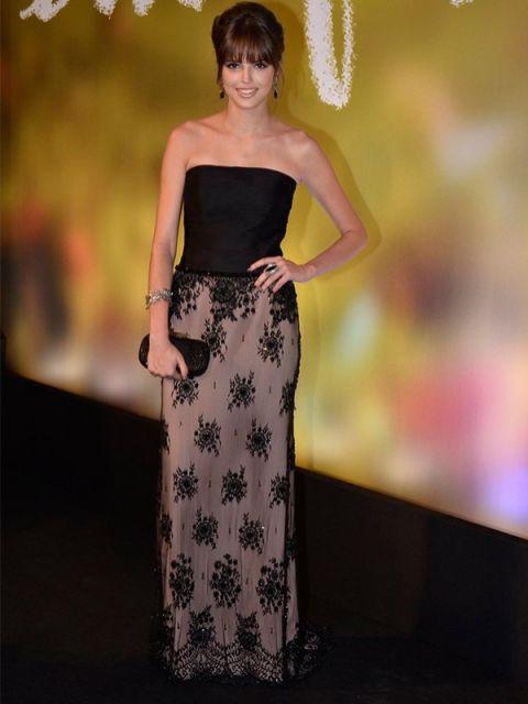 Agatha Moreira usa vestido longo preto com detalhes em tom nude, com bolsa preta carteira preta.