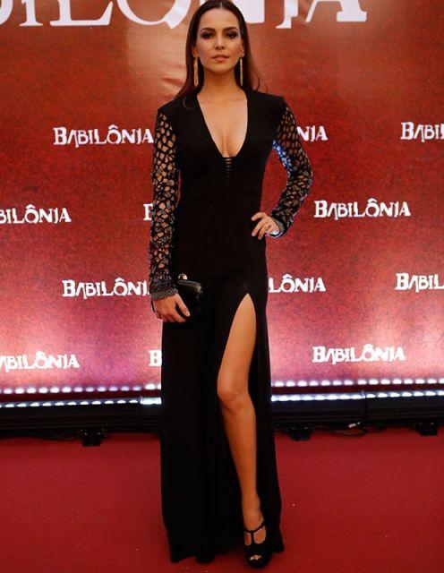 Modelo usa vestido preto decotado, com fenda e bolsa preta carteira.