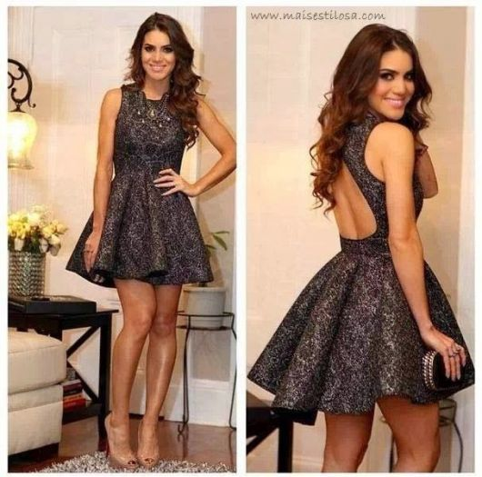 Camila Coelho com bolsa preta de festa e vestido cinza rodado com sapato nude.