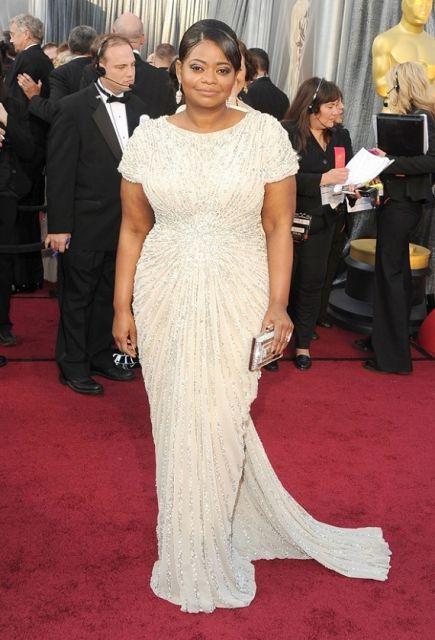 Modelo veste vestido branco longo sem muitos detalhes com clutch prateada.
