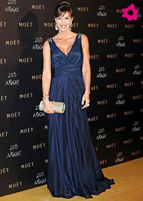 Modelo usa vestido azul longo, decote profundo e bolsa prata de mão.