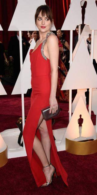 Modelo usa look com vestido vermelho com fenda, bolsa cinza escuro e sapato prata.
