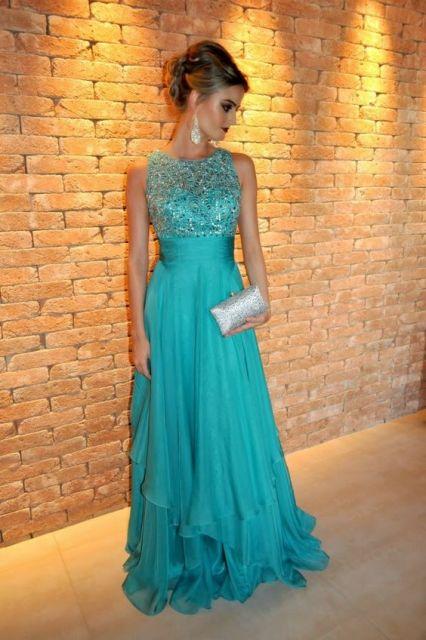 Modelo veste vestido azul turquesa com detalhes no busto, sem decote com bolsas e brincos em tom de prata.