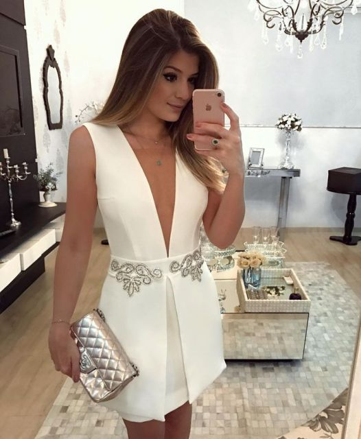 Modelo veste vestido branco curto com bolsa prat textura diferente.