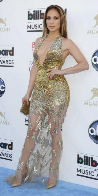 Jennifer lopez veste vestido com detales dourados e transparencias.