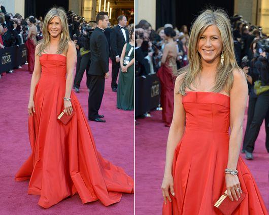 Jennifer Aniston usa vestido laranja com bolsa dourada.