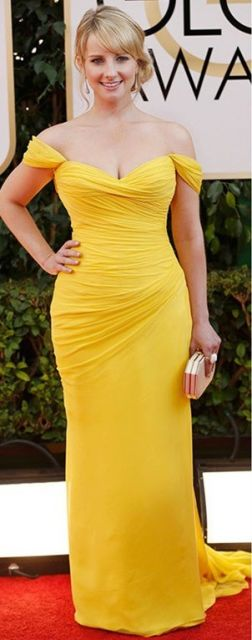 Modelo usa vestido amrelo com bolsa carteira dourada.