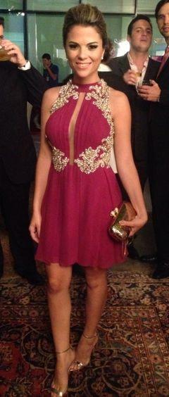 Modelo usa vestido cor vinho, bolsa de festa dourada e sapato na mesma cor.
