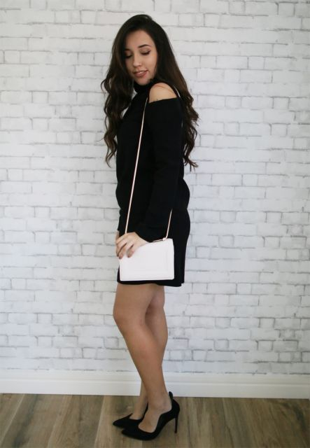 Modelo usa vestido preto, sapato no mesmo tom e bolsa branca.
