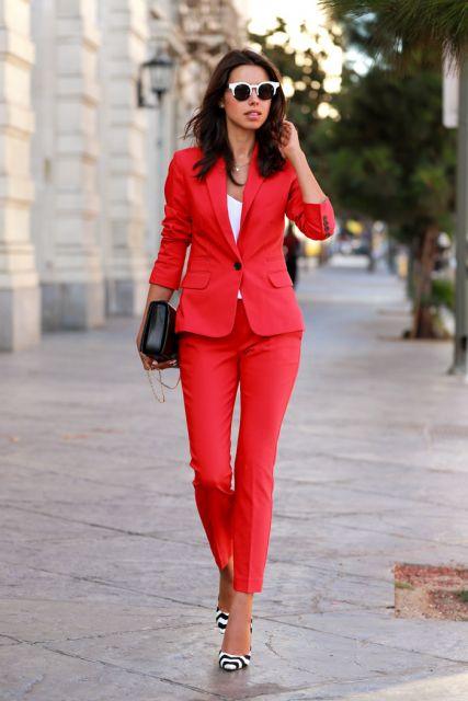 Modelo usa terninho vermelho, bolsa preta de festa e sapato estampa preto e branco.