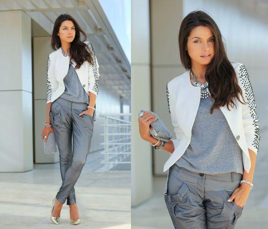 Modelo usa calça cinza, blusa cinza e blazer branco, com clutch prateada e sapato scarpin metalizado.