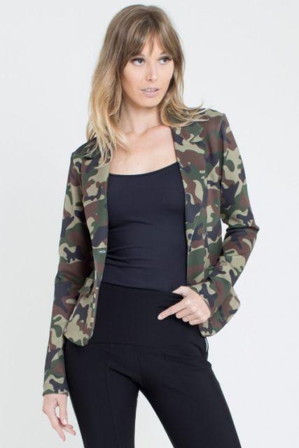 modelo usa blusa preta, calça na mesma cor e camisa camuflada, com cabelo solto.