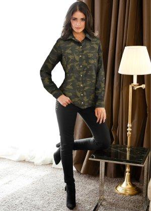 modelo veste calça preta, camisa fechada camuflada e botinha preta.