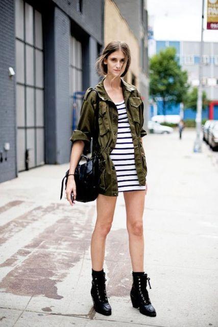 modelo usa vestido listrado, camisa camuflada e cuturno preto.