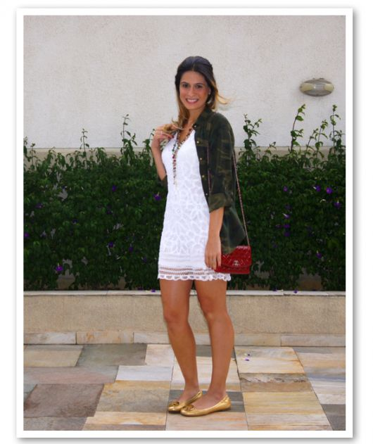 modelo veste vestido branco e sapatilha dourada, bolsa vermelha e camisa verde camuflada.