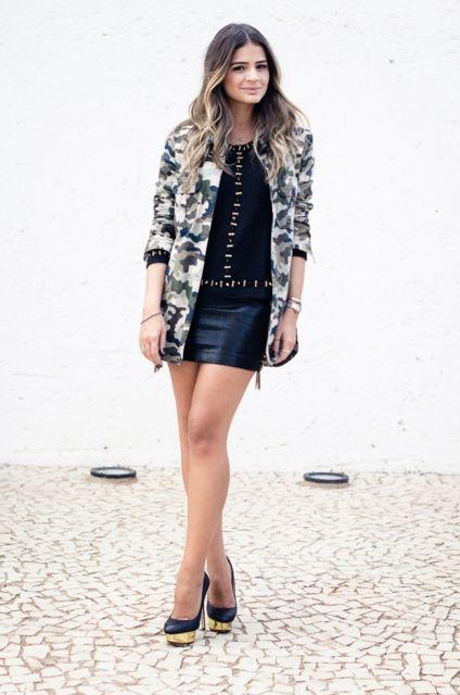 modelo veste vestido preto, camisa camuflada e sapato de salto alto com detalhes em dourado.