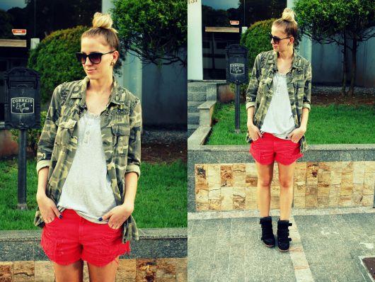 modelo usa short vermelho, camisa camuflada, blusa cinza e tenis preto.