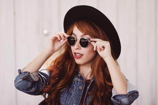 modelo usa óculos preto, chapeu na mesma cor e camisa jeans.