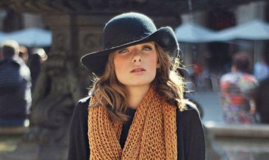 modelo veste cachecol em tons terrosos, blusa e chapeu na cor preta.