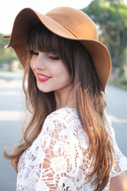 modelo veste chapéu floppy cor amarelo queimado com blusa de renda branca.