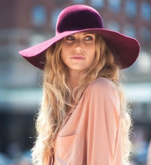 modelo usa blusa rosê com chapeu floppy roxo.