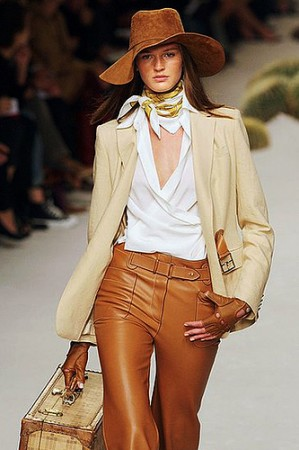 modelo usa calça em tons terrosos, blusa branca, blazer e chapeu country.