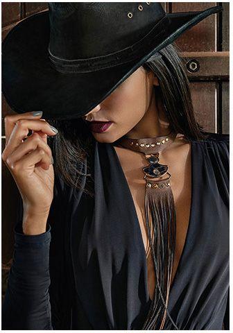 modelo usa blusa preta e chapéu na mesma cor.