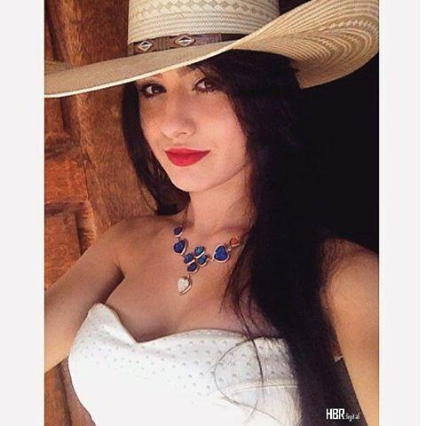 modelo usa blusa branca, tomara que caia com chapéu de palha country e colar azul e branco.