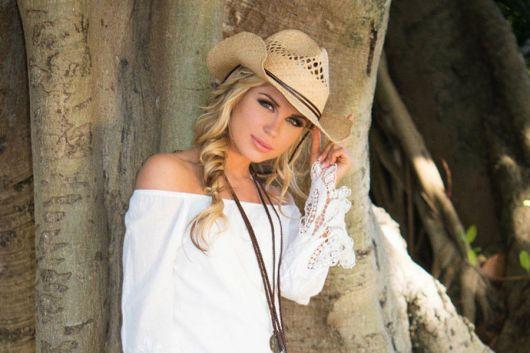 modelo veste chapeu pralana, blusa branca e cabelos soltos.