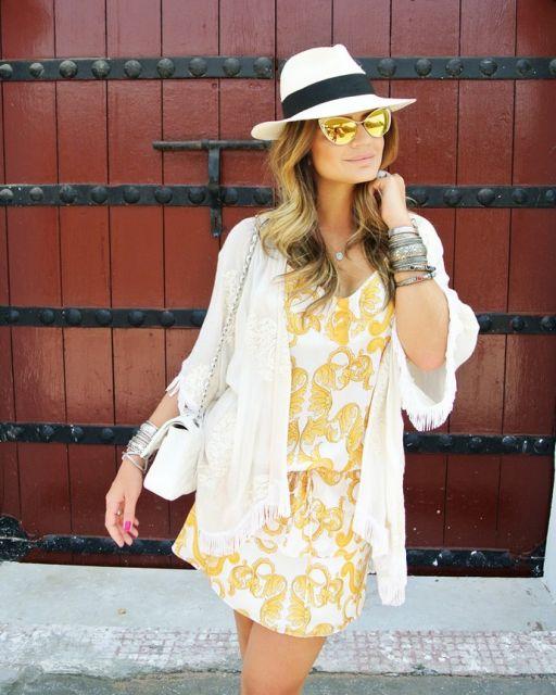Thássia Naves veste look com vestido amarelo, sobreposição branca , oculos espelhado, bolsa branca e chapéu branco e preto.