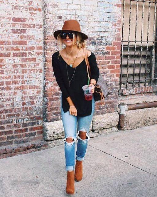 modelo usa calça jeans, blusa preta e sapato . bolsa e chapéu em tons terrosos.