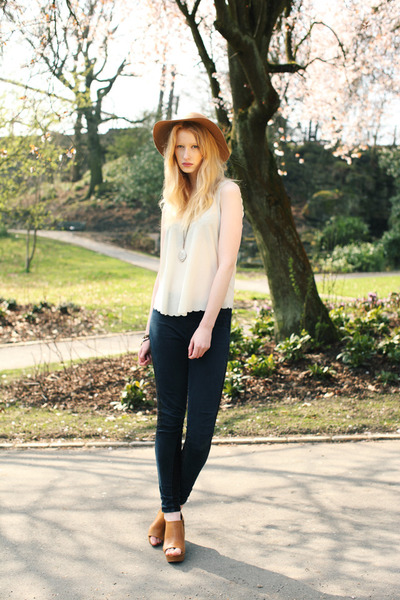 modelo veste calça jeans preta, blusa regata, sapato de salto alto e chapeu.