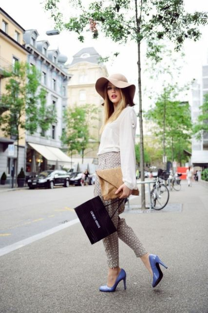 modelo usa chapeu nude, camisa branca, calça em alfaiataria e sapato scarpin lilás.