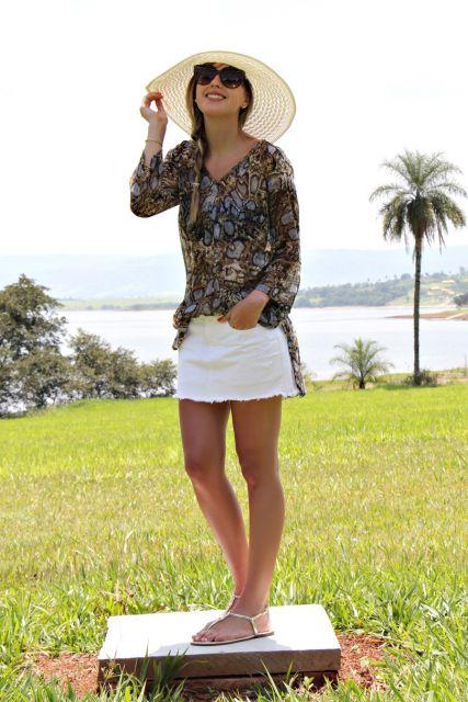 modelo veste saia branca, blusa estampada e rasteirinha.