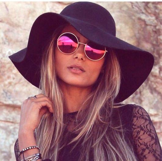 modelo usa chapéu preto com óculos espelhado cor de rosa.