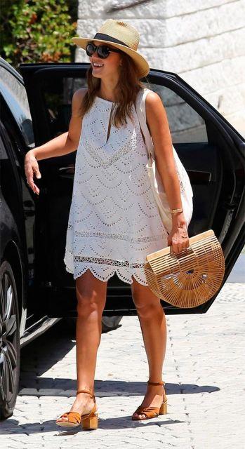 modelo usa vestido largo, chpéu , bolsa e sapato no mesmo tom terroso.