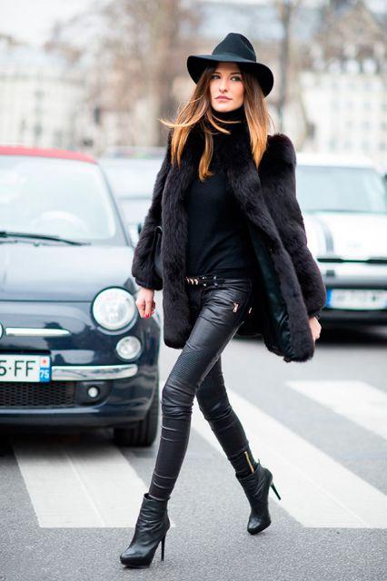 modelo veste calça jeans, casaco, blusa, sapato e chapéu em preto.