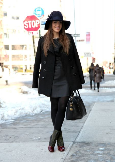 modelo usa vestido preto, bolsa, meia sapato e chapéu também em tons de preto.