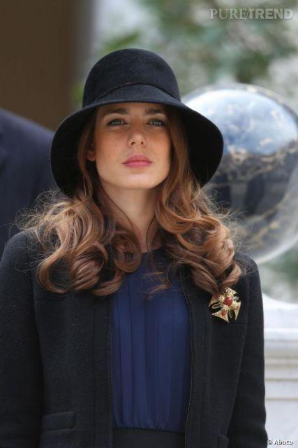modelo usa chapeu preto, com blusa azul e blazer preto.