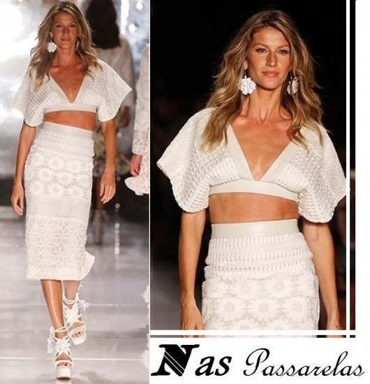 Modelo gisele bundchen usa cropped branco, com saia midi no mesmo tom e sapato branco.