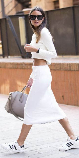 Modelo usa blusa cropped branca manga longa, tenis branco, saia branca e bolsa bege.
