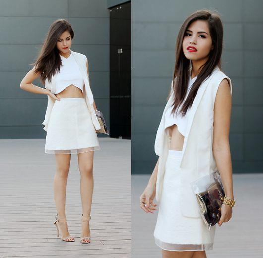 Modelo veste saia branca, sapato nude, colete branco e blusa cropped branco.